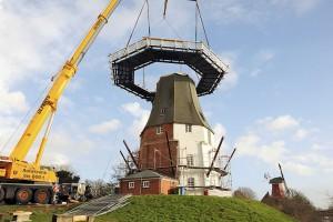 Ein Etappenziel beimWiederaufbau der Greetsieler Zwillingsmühle ist erreicht: Die Galerie ist an Ort und Stelle. Foto: Stromann