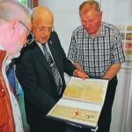 Rüdiger Hessling (Mitte) zeigt den interessierten Mühlenfreunden seine ersteigerten Exponate. BILD: ANNA GRAALFS